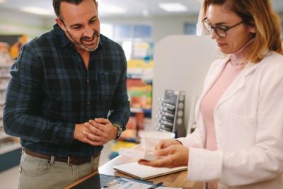 female pharmacist holding medicine box giving advice to customer in chemist shop